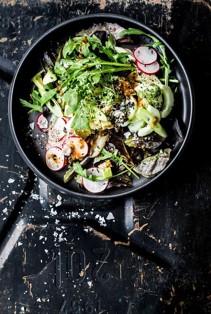 A green salad with radishes, spring onion and tahini