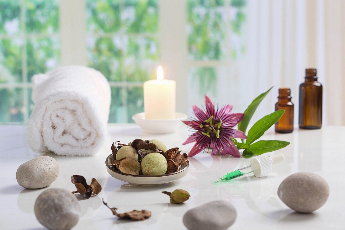 An arrangement of a towel, stones, a candle, a flower and a pipette to represent wellbeing