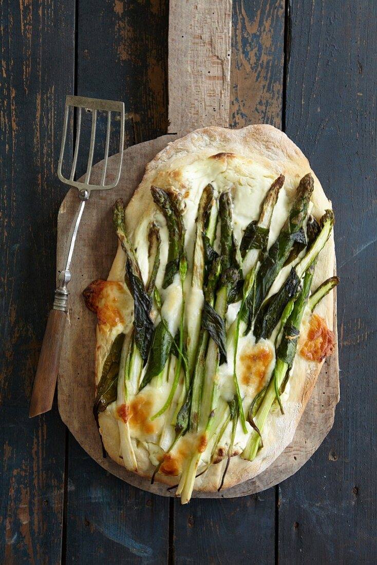 Wild garlic and asparagus pizza with parmesan on a pizza shovel (seen from above)