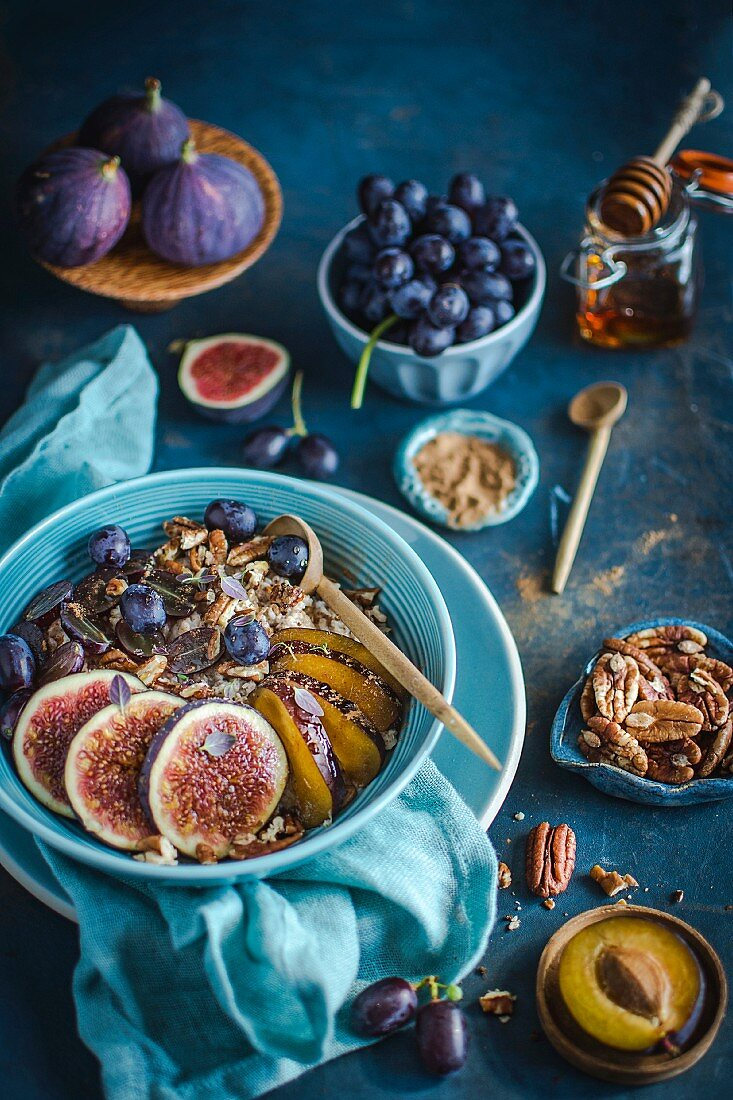 Porridge with figs, plums, grapes, pecan nuts, honey and cinnamon
