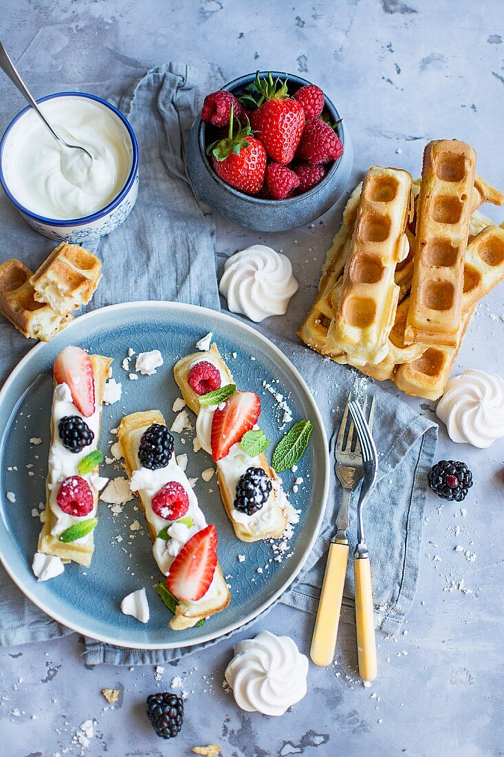 Waffles with cream, raspberries, strawberries, blackberries and mint