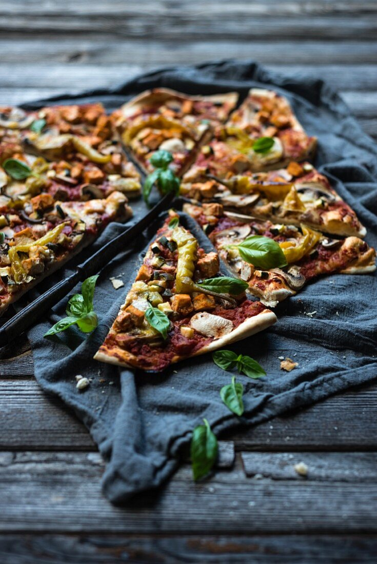 A vegan pizza with pepperoni, mushrooms, courgette, tofu and a cheese alternative