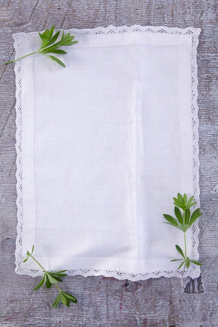 Fresh woodruff leaves on a white linen cloth