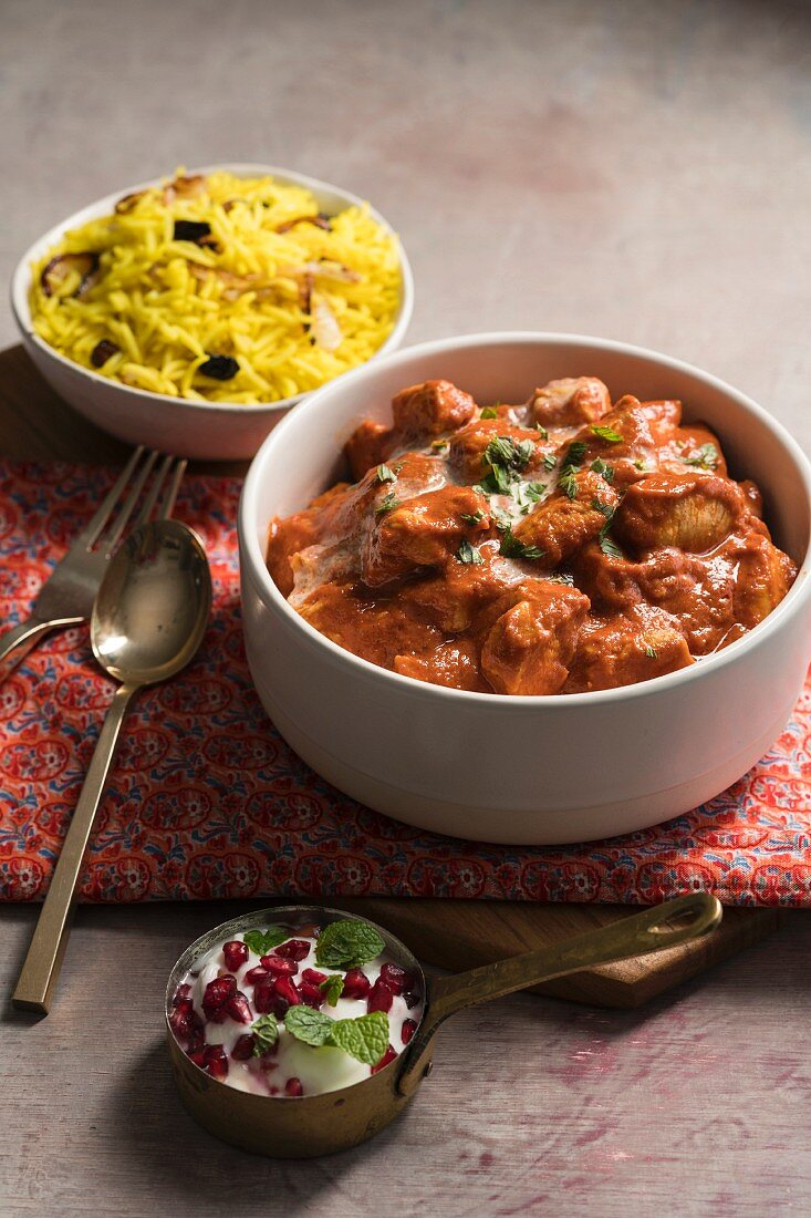 Butter chicken curry with turmeric rice and yoghurt sauce (India)
