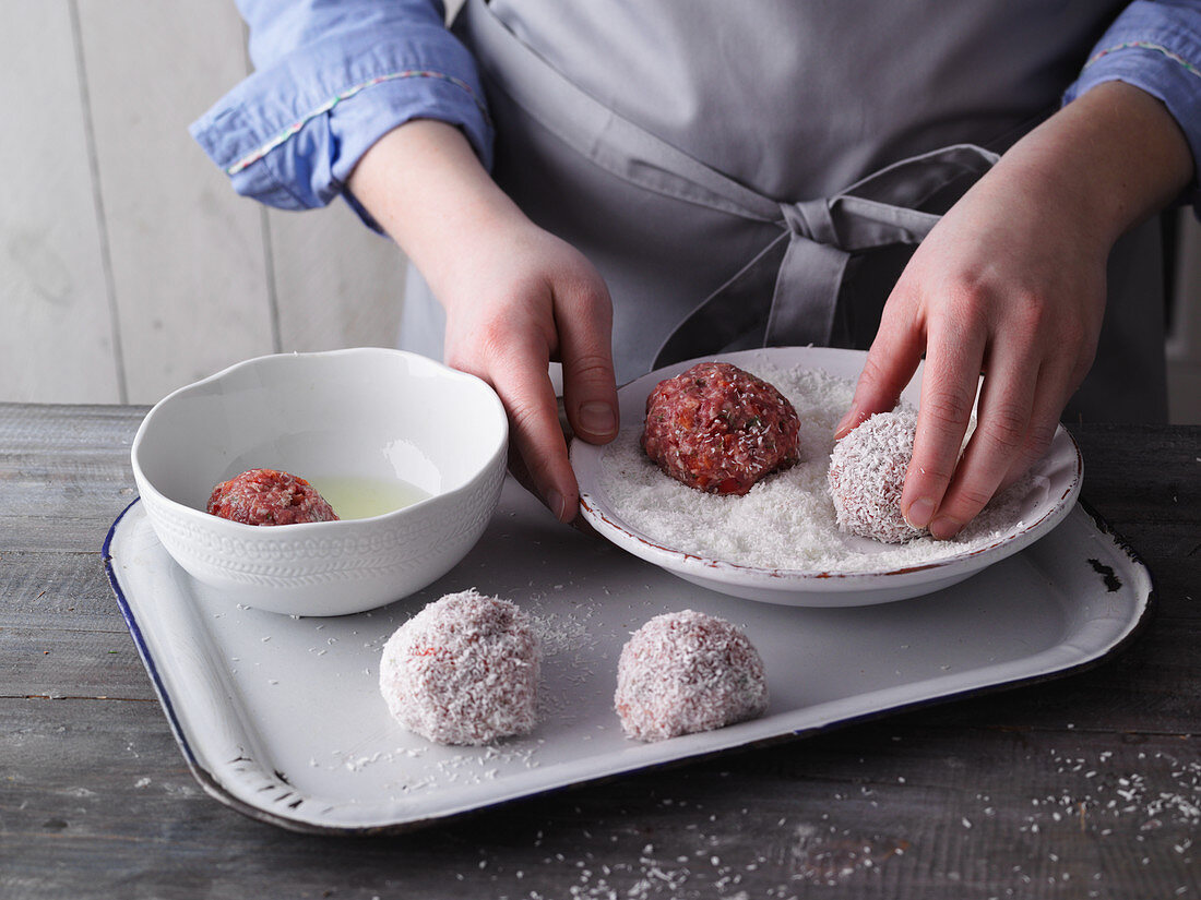 Meatballs being rolled in coconut flakes