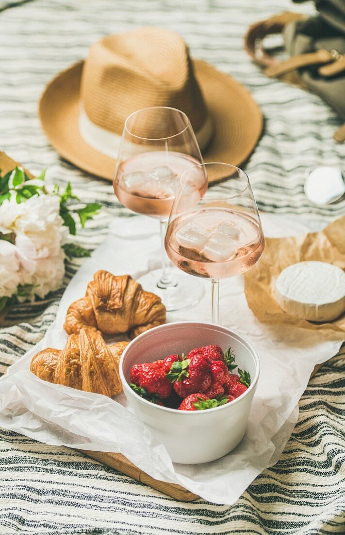 Rosé wine, strawberries, croissants, flowers and a straw hat on a picnic blanket