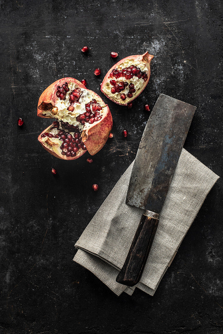 Pomegranate, sliced, with cleaver