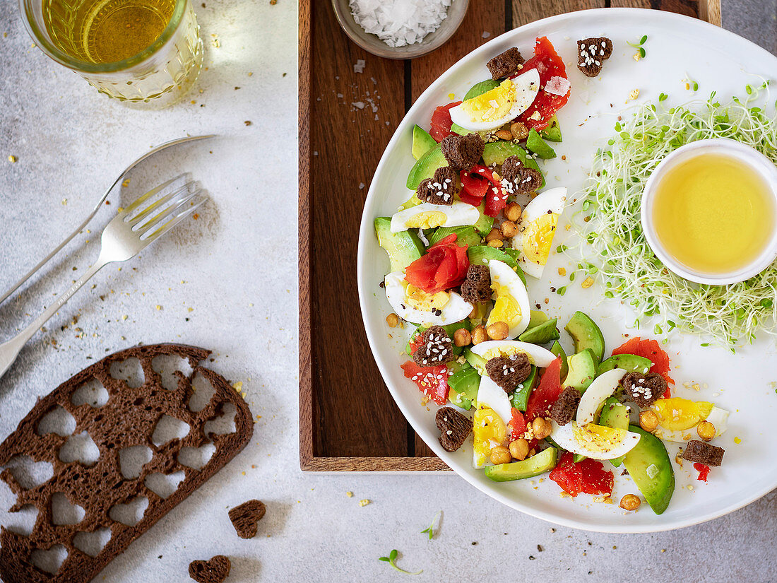Bread salad with smoked salmon, avocado and egg on white plate