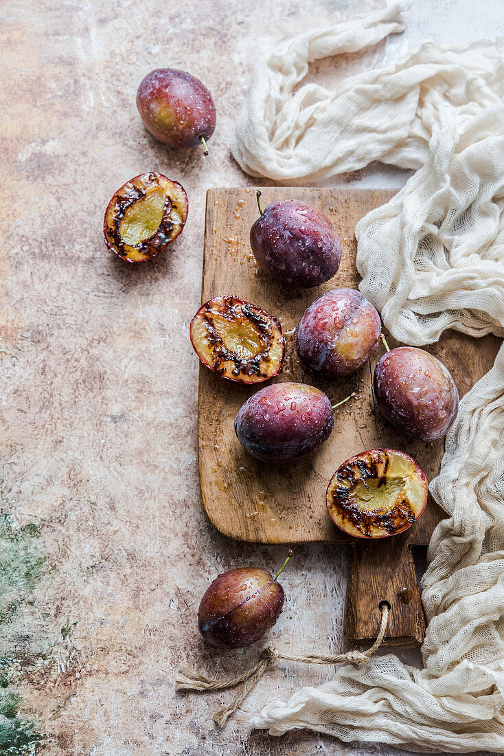Fresh and grilled plums on a wooden board