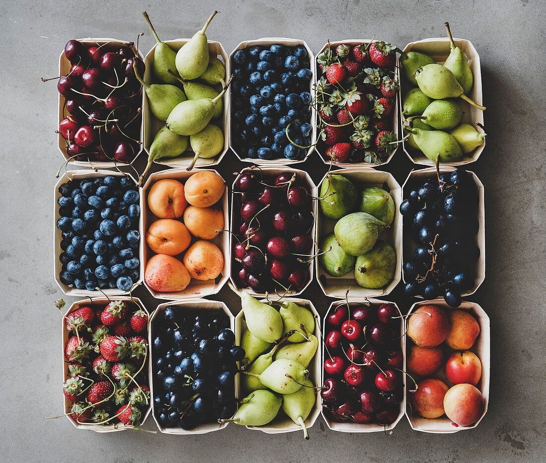 Summer fruit and berry variety: Flat-lay of strawberries, cherries, grapes, blueberries, pears, apricots, figs in wooden eco-friendly boxes