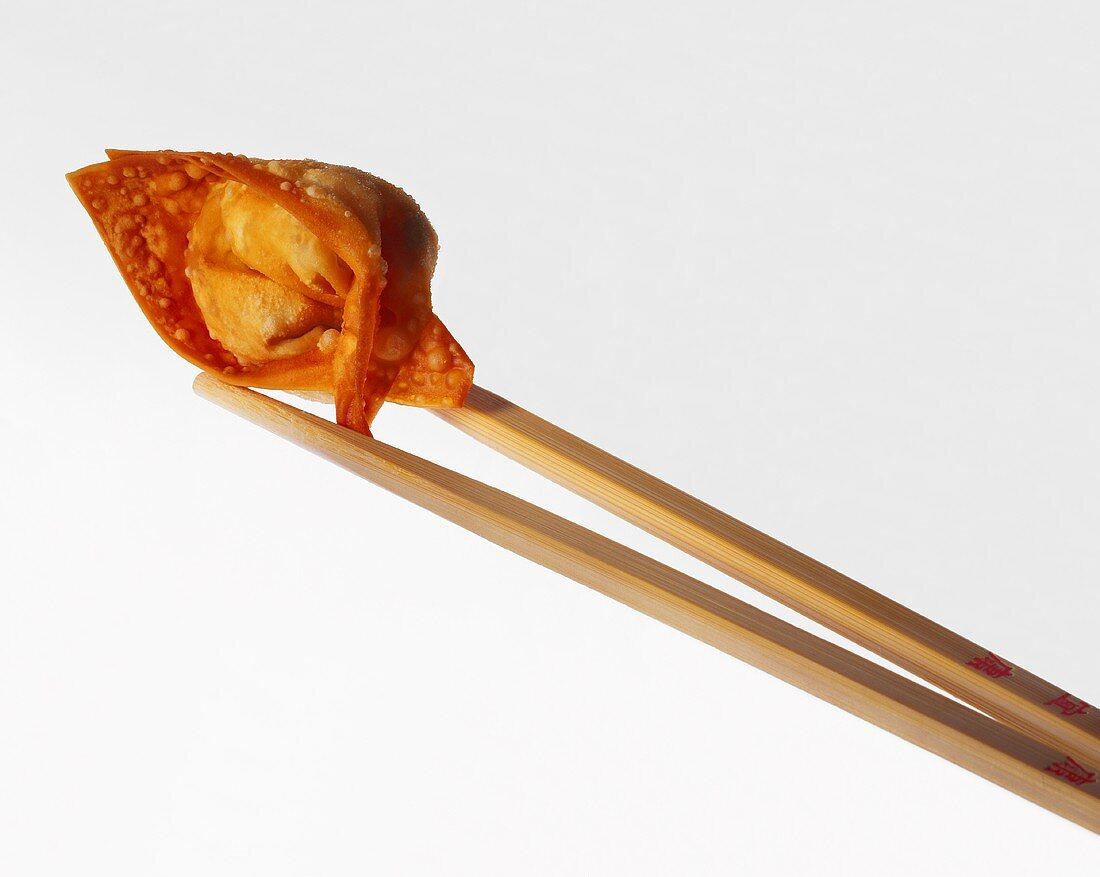 Wooden chopsticks holding a deep-fried won ton (pastry parcel)