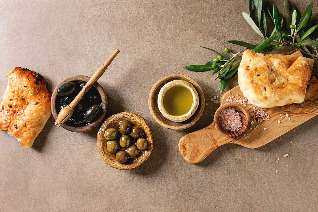 Variety of green and black whole olives in olive oil served in bowls with fresh baked ciabatta bread