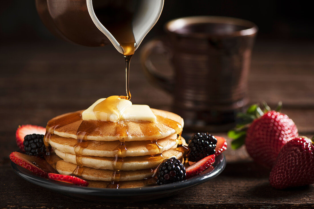 Maple Syrup Pouring Over a Stack of Pancakes