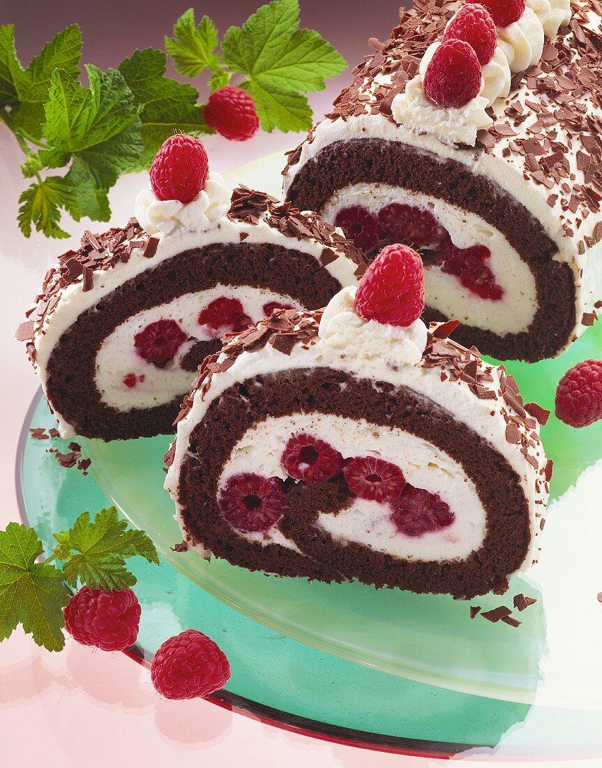 Chocolate sponge roulade filled with cream & raspberries