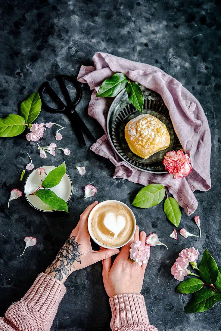 A cup of coffee with a milk foam heart served with coconut biscuits