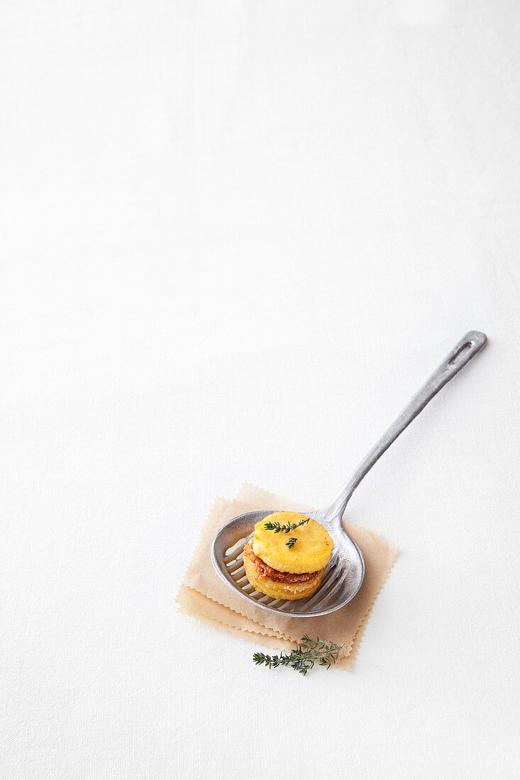 A fried polenta macaron with sausage and cheese filling