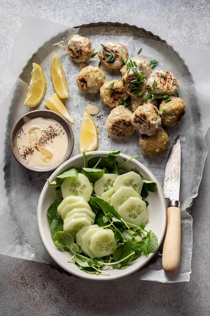 Köttbullar serviert mit cremiger Sauce und Gurkensalat auf Tablett (Schweden)