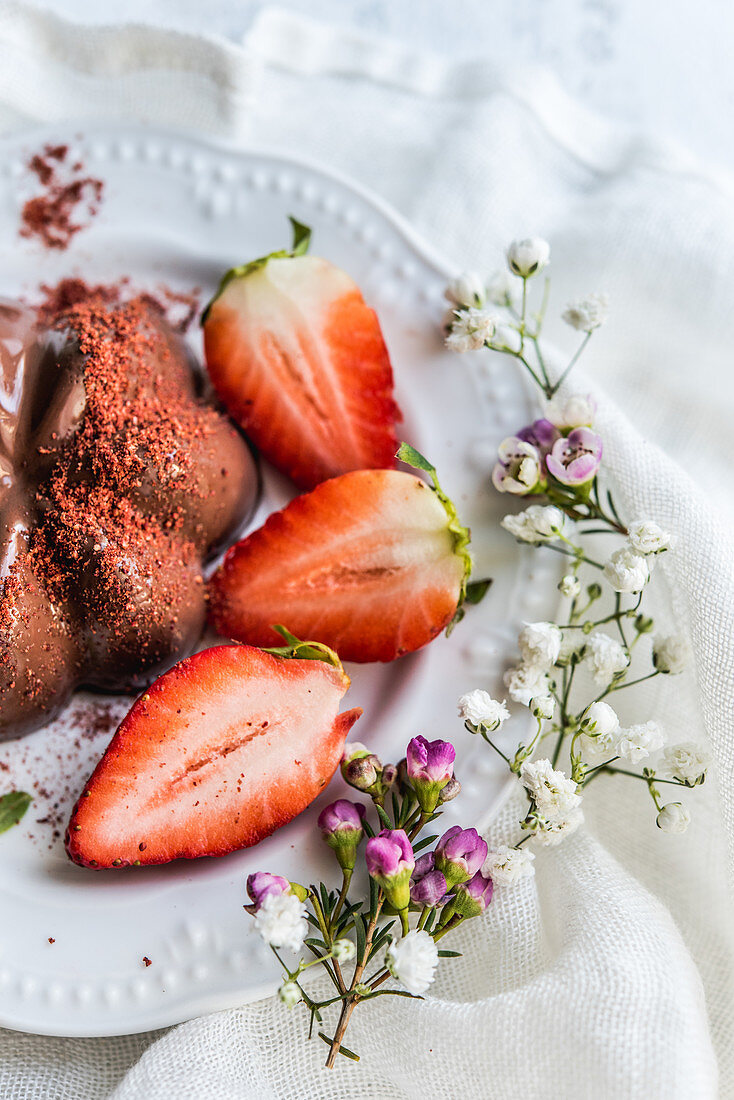 Chocolate pudding decorated with strawberries and strawberry powder