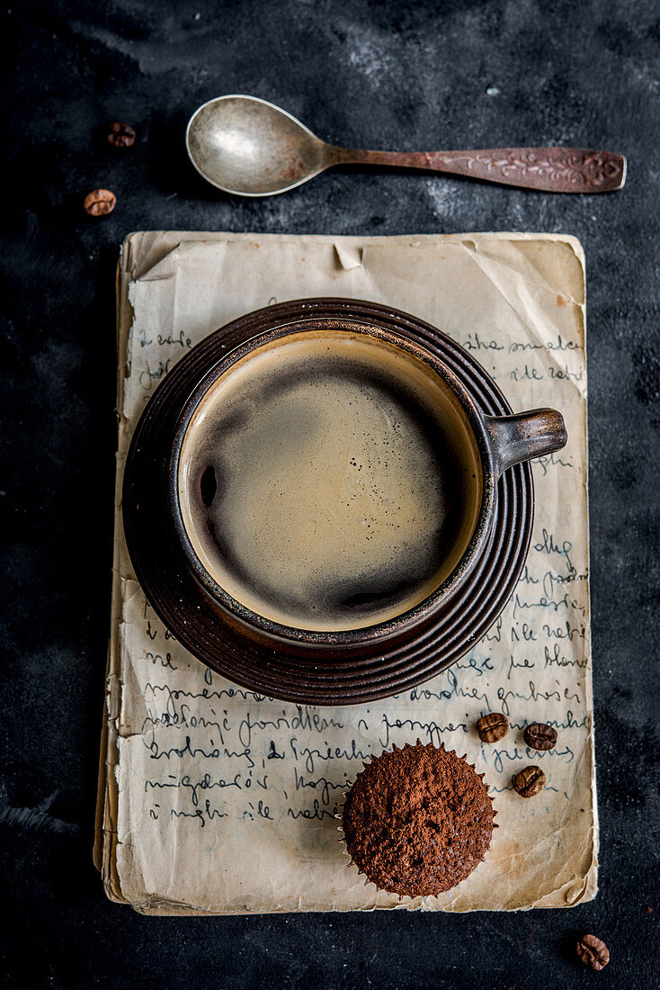 Coffee beans in a bowl and a sieve with cocoa powder