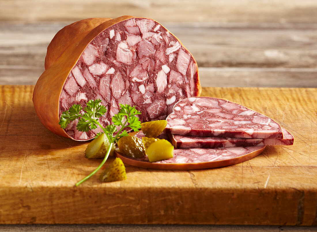A large blood sausage in skin, sliced on a wooden board