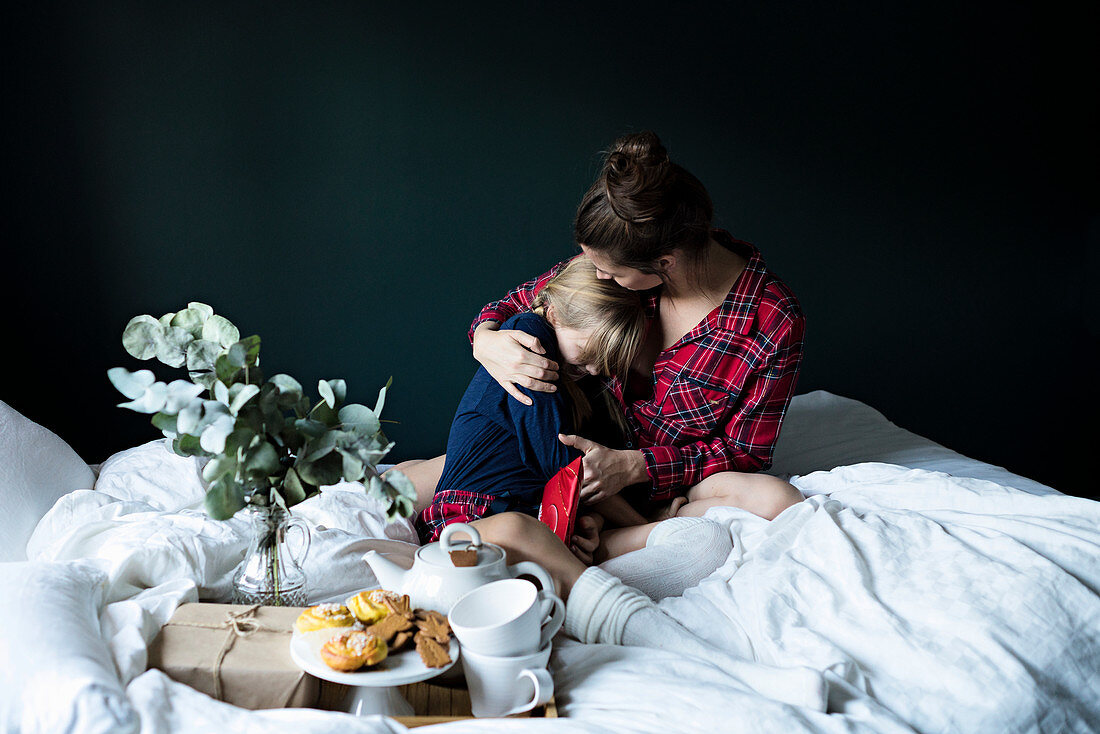 A mother and daughter having breakfast in bed
