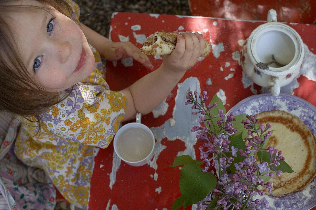 A little girl having a tea party in garden