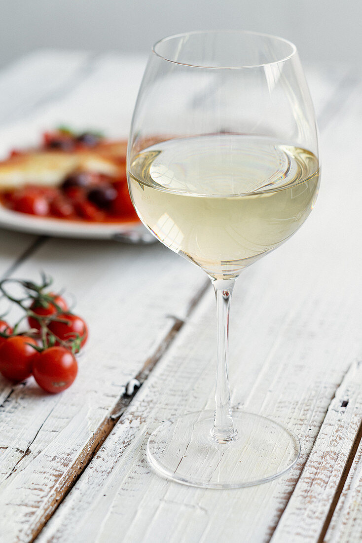 A glass of white wine on a white wooden table