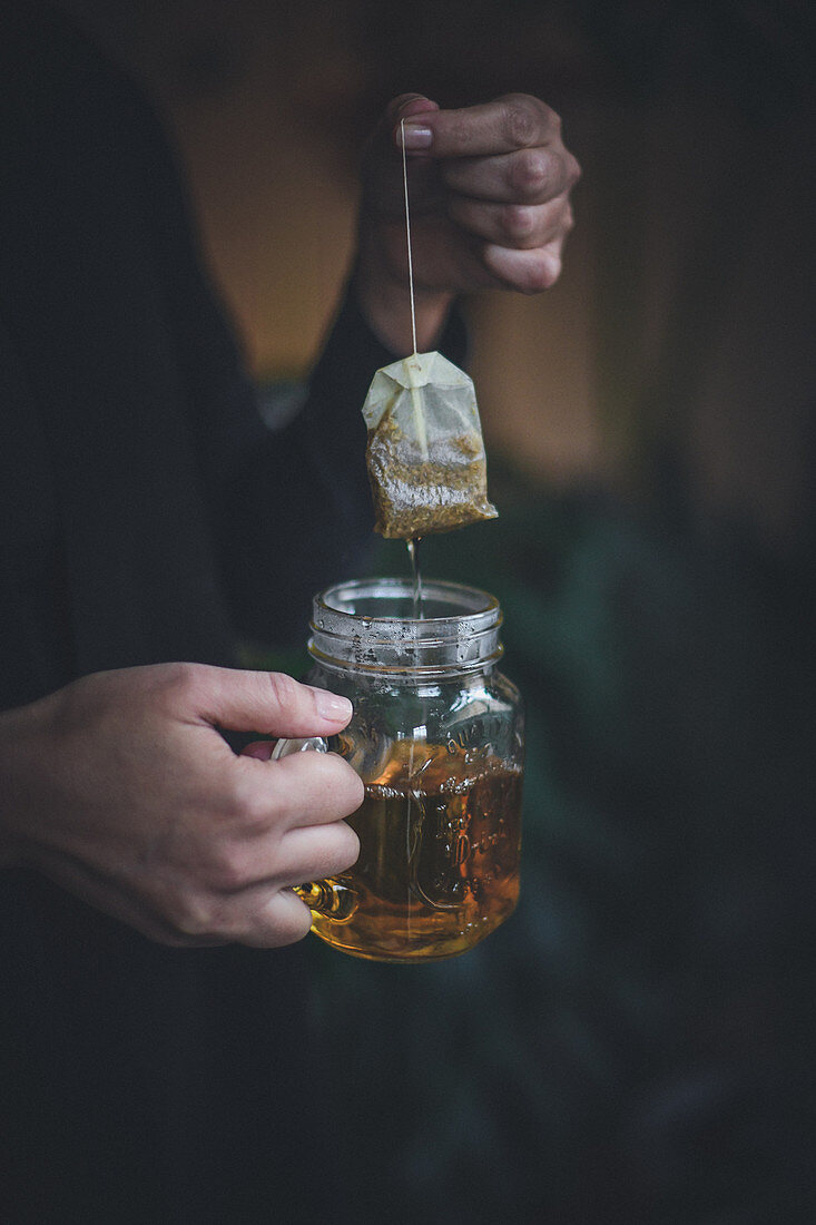 A woman holding a dripping teabag and a hot herbal tea