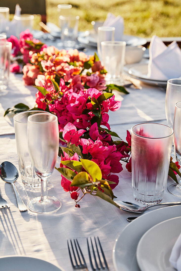 Set table outdoors decorated with garland of bougainvillea flowers