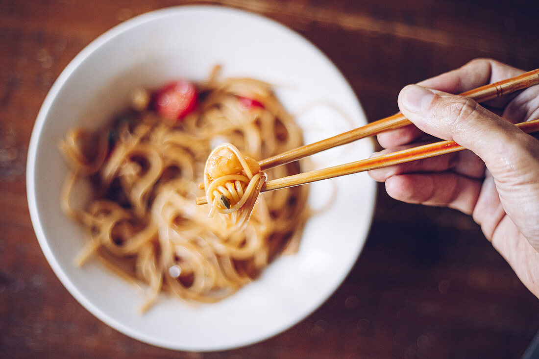 Person holding shrimp by wooden chopsticks while enjoying noodles
