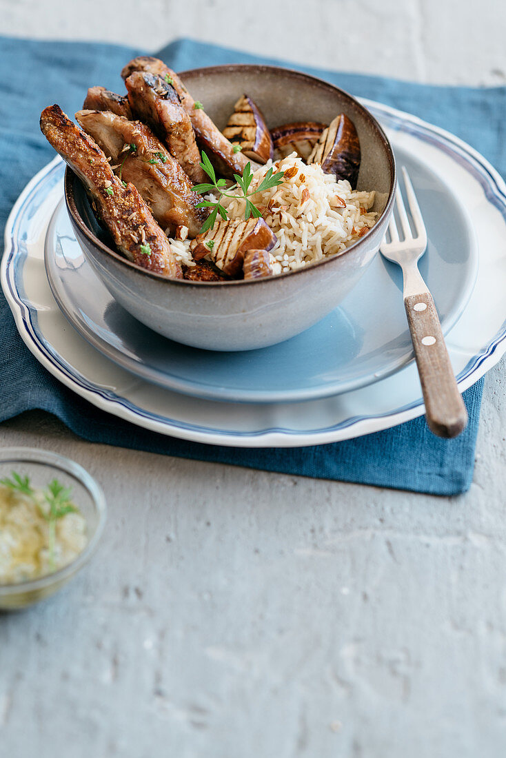 Grilled ribs in caraway and lemon marinade with roasted almonds, rice and grilled aubergines