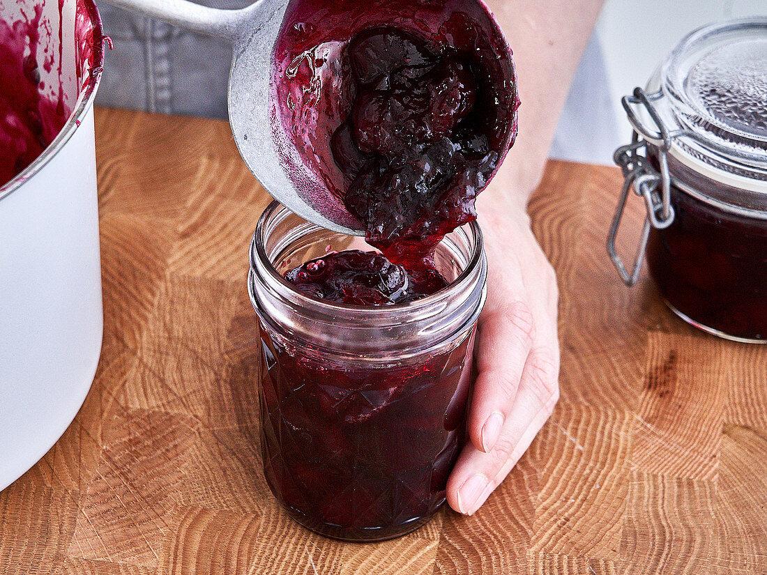 Cherry jam being transferred to jars