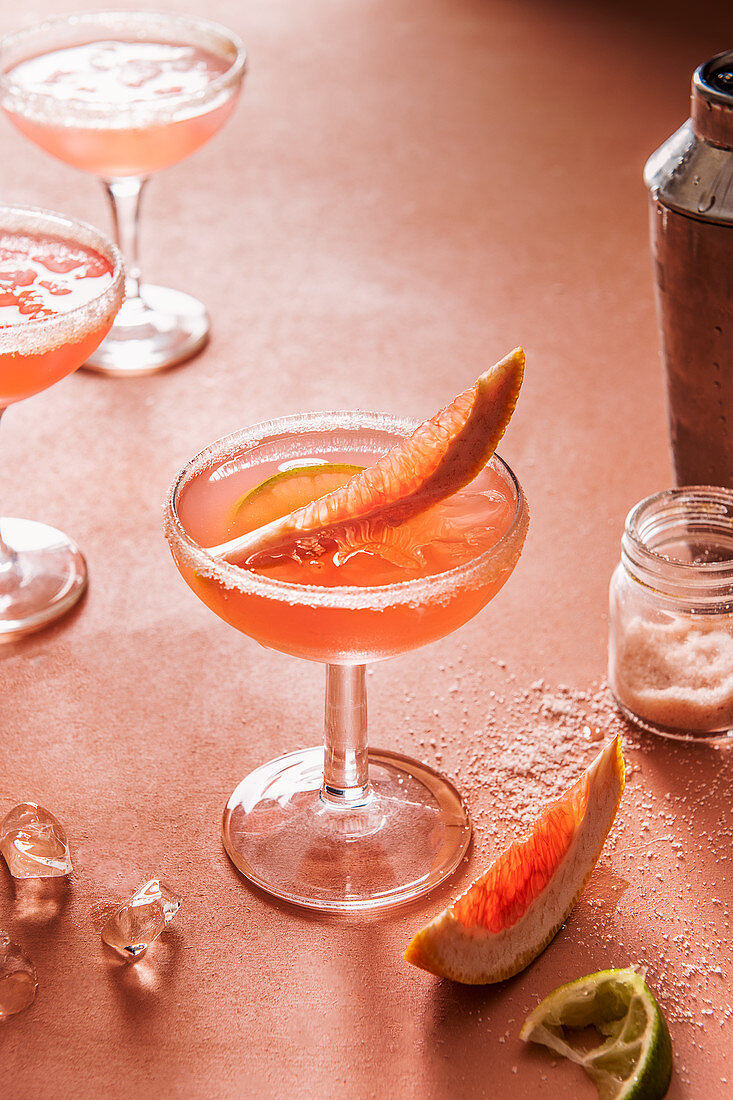 Grapefruit margarita cocktail on ice with pink salt and lime