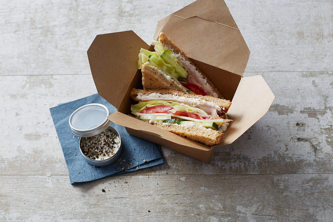 A club sandwich with ham, cheese and turkey breast 'to go'