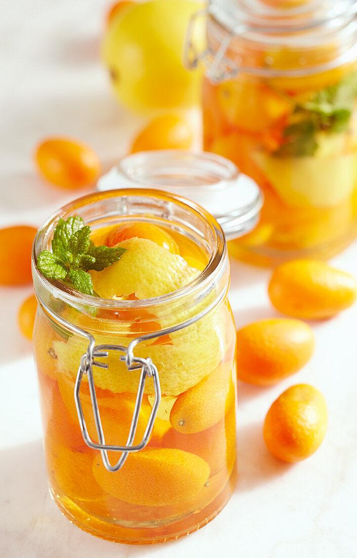 Homemade kumquat vinegar in jars with whole fruits, lemon zest and fresh mint