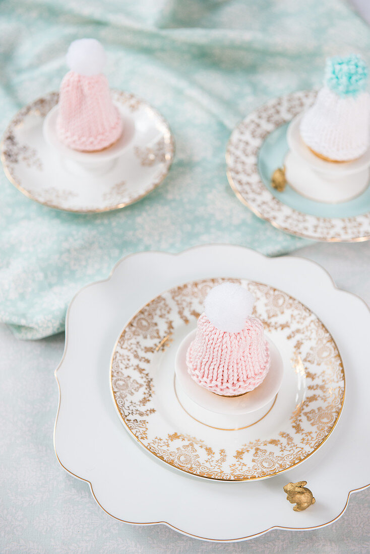 Knitted bobble-hat egg cosies on vintage-style plates