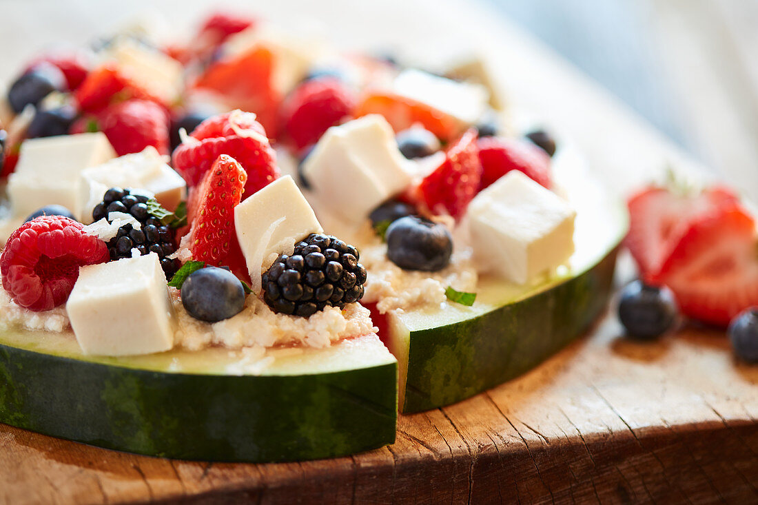 Berry salad with mozzarella cheese served on watermelon slices