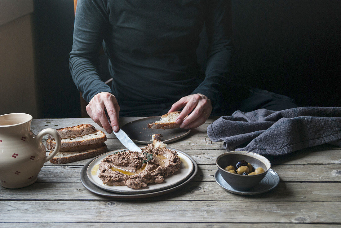A man spreading lentil and shiitake cream on bread