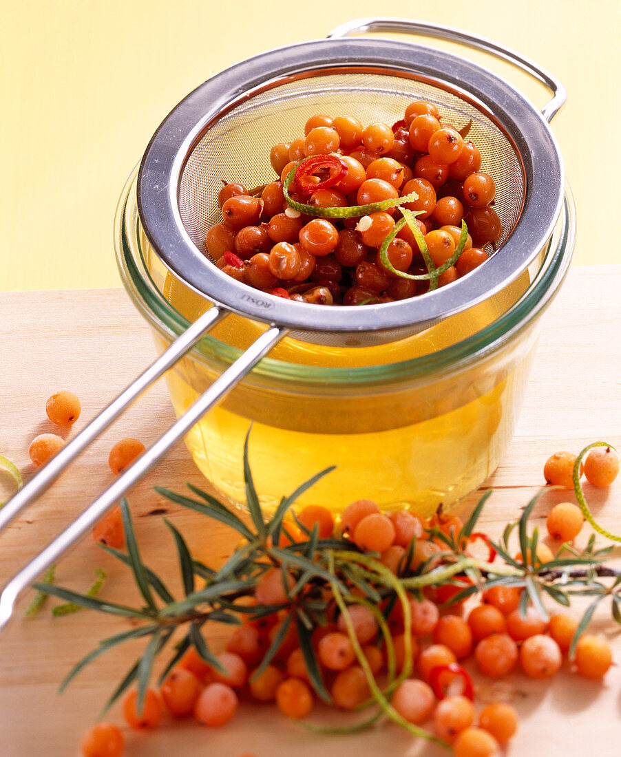 Homemade vinegar with fresh sea buckthorn berries, lime zest and chili