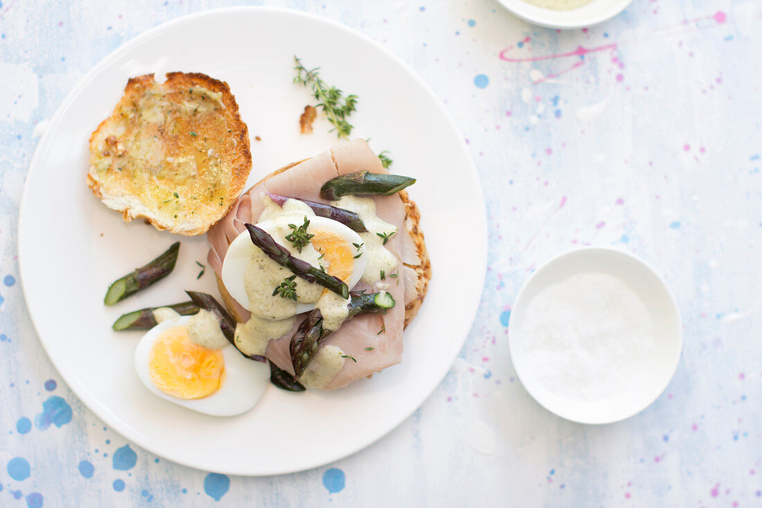 Purple asparagus and boiled egg breakfast bun with ham, thyme and a drizzle of Hollandaise