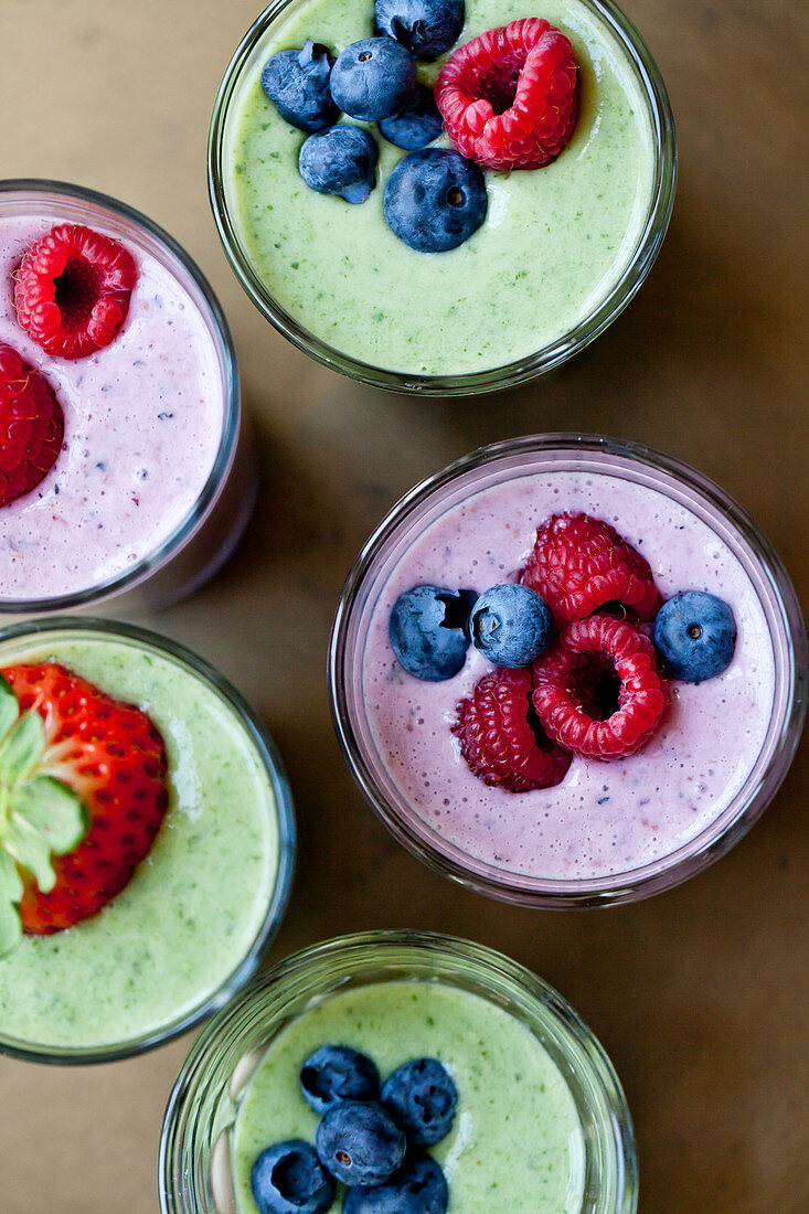 Berry smoothies and green smoothies, topped with fruit
