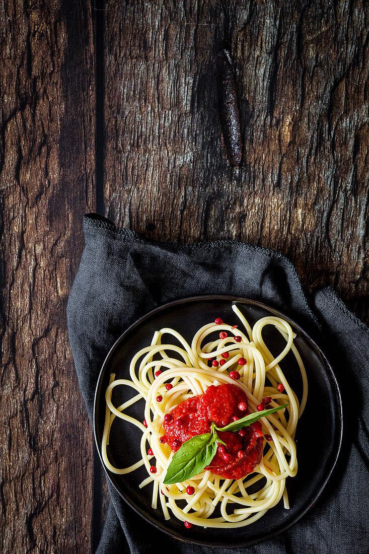Spaghetti with tomato sauce on dark background