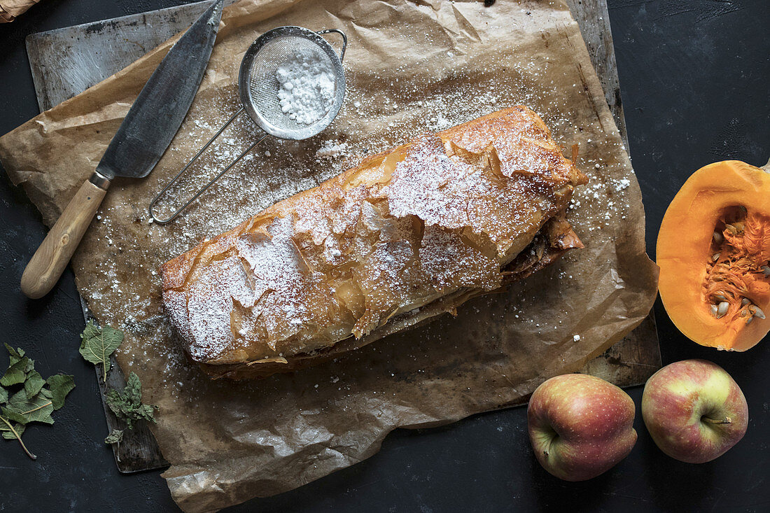 Sharp knife lying on parchment near delectable pumpkin and apple strudel