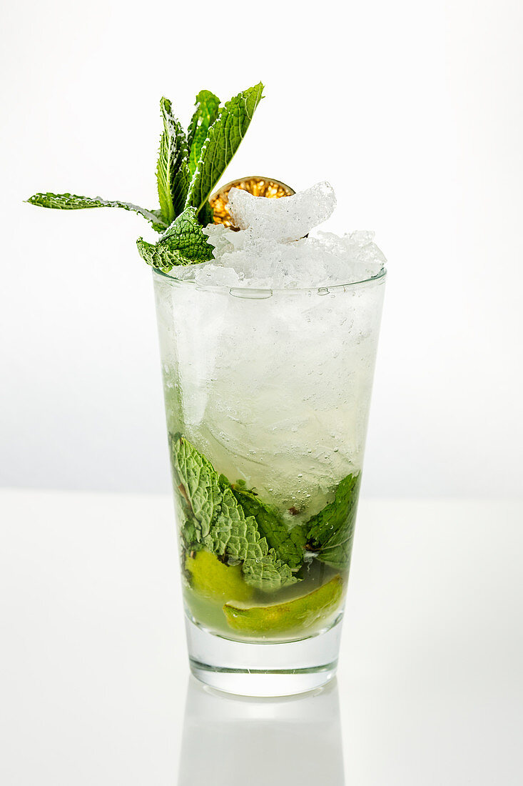 High glass with traditional Mojito cocktail garnished with dried lime and mint on white background