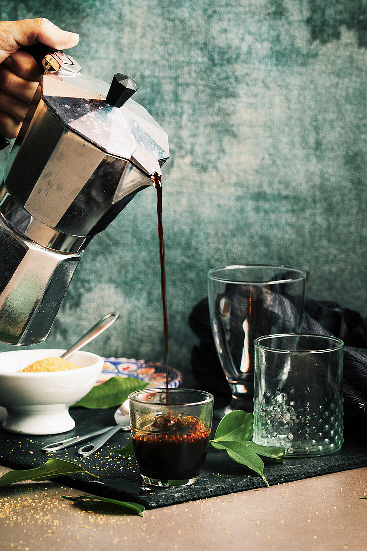 Hand serving coffee in crystal glass
