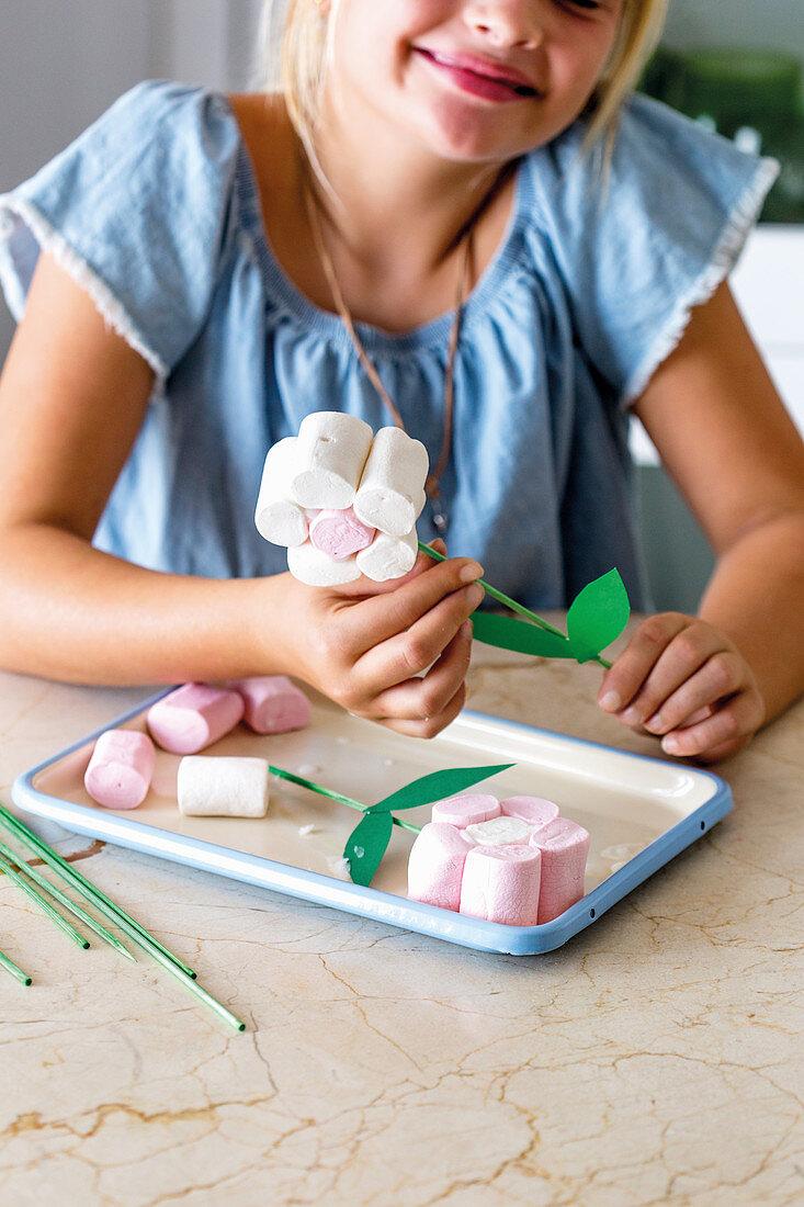 Girl making marshmallow flowers