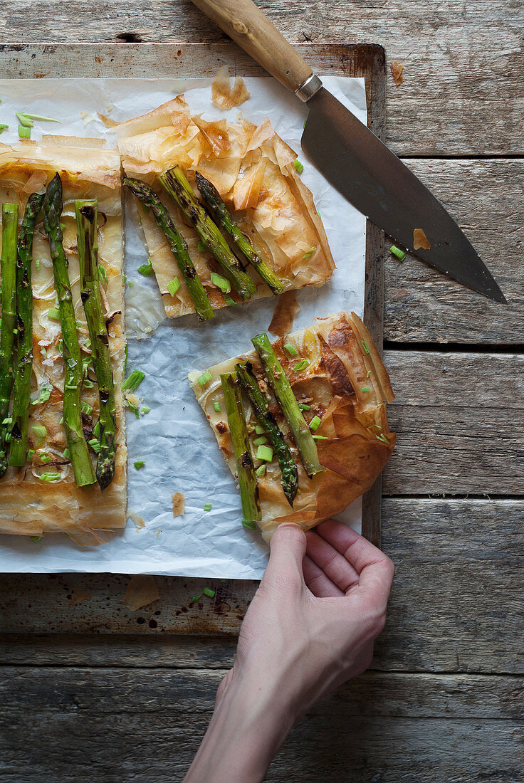 A hand taking a piece of puff pastry tart with green asparagus and onions