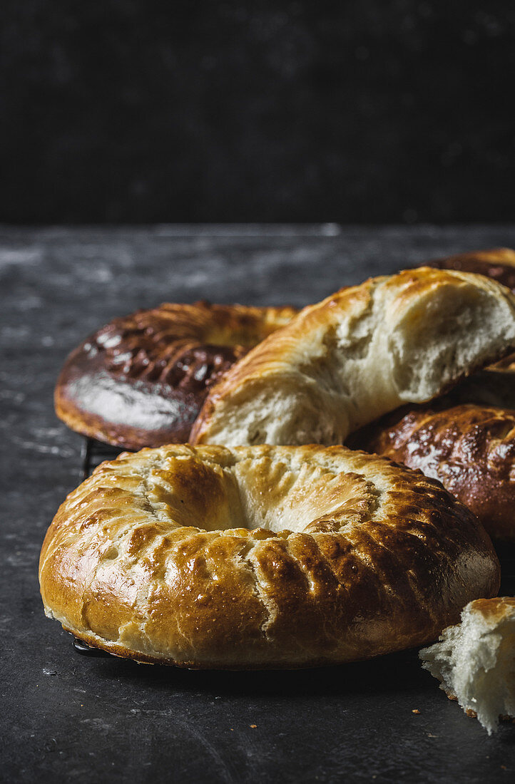 Closeup shot of delicious fresh brioche crowns lying on marble tabletop in dark room