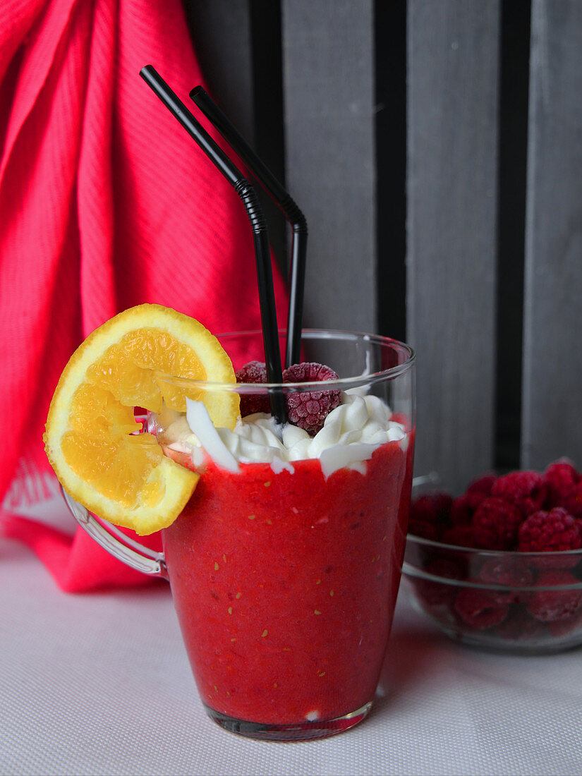 A pink smoothie with raspberries