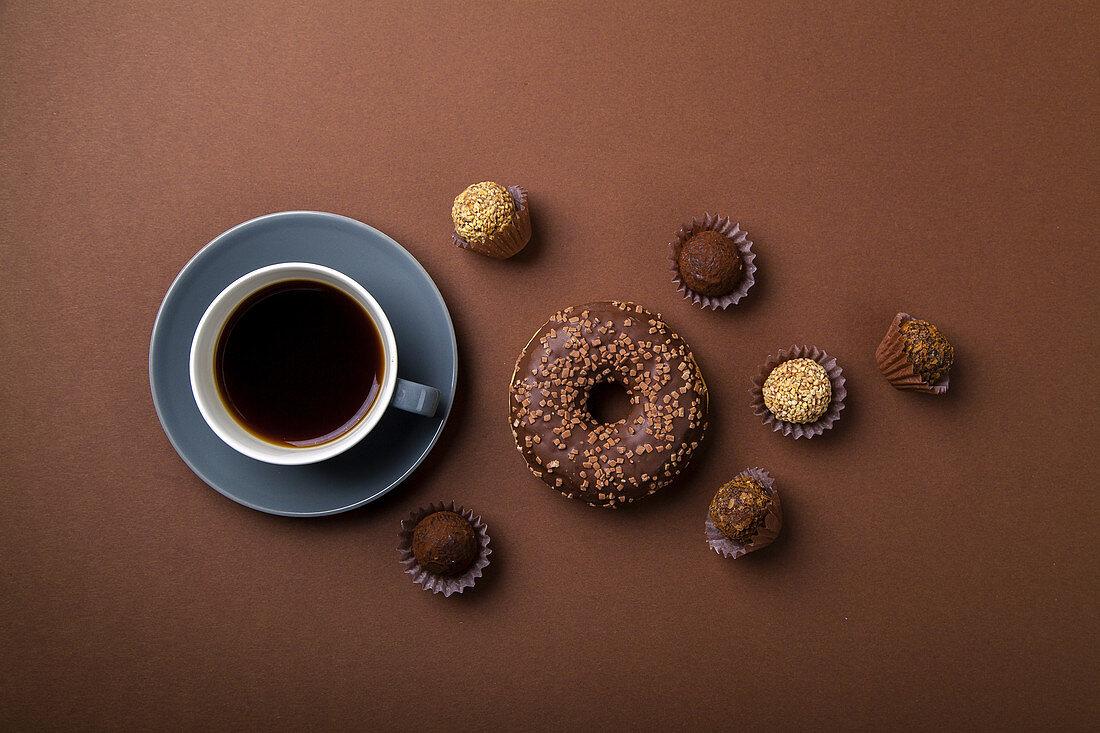 Schokoladen-Donut und verschiedene Trüffel zur Tasse Kaffee